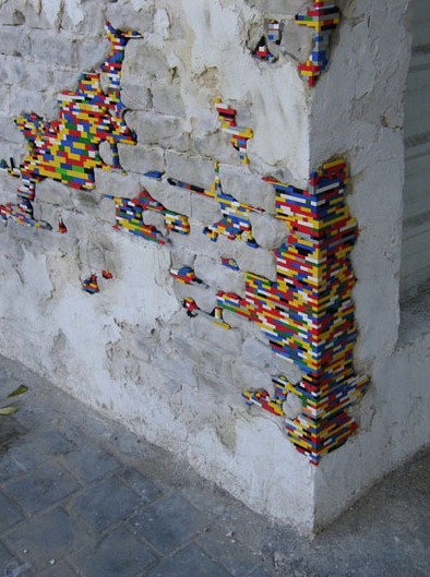 Beauty of Repair lego filled cracks on brick wall