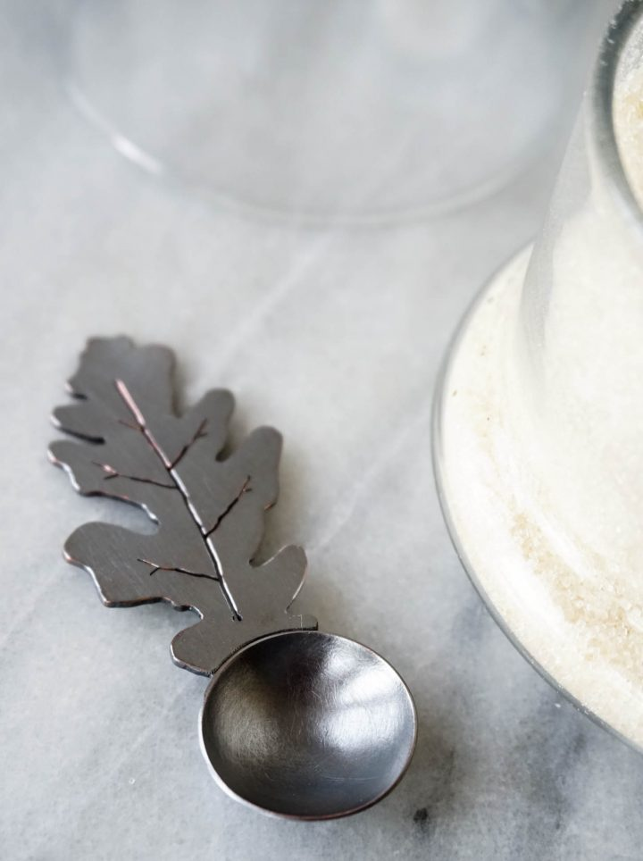 copper leaf sugar spoon with glass bell jar on marble